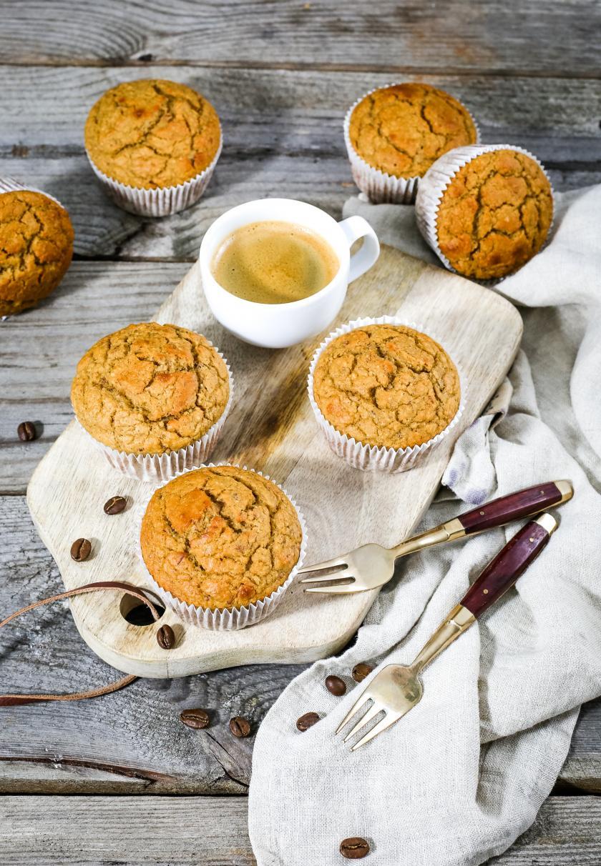 Merere Low Carb Vanille-Espresso-Muffins auf einem Holzbrett angerichtet. Dabei steht eine Tasse Espresso.