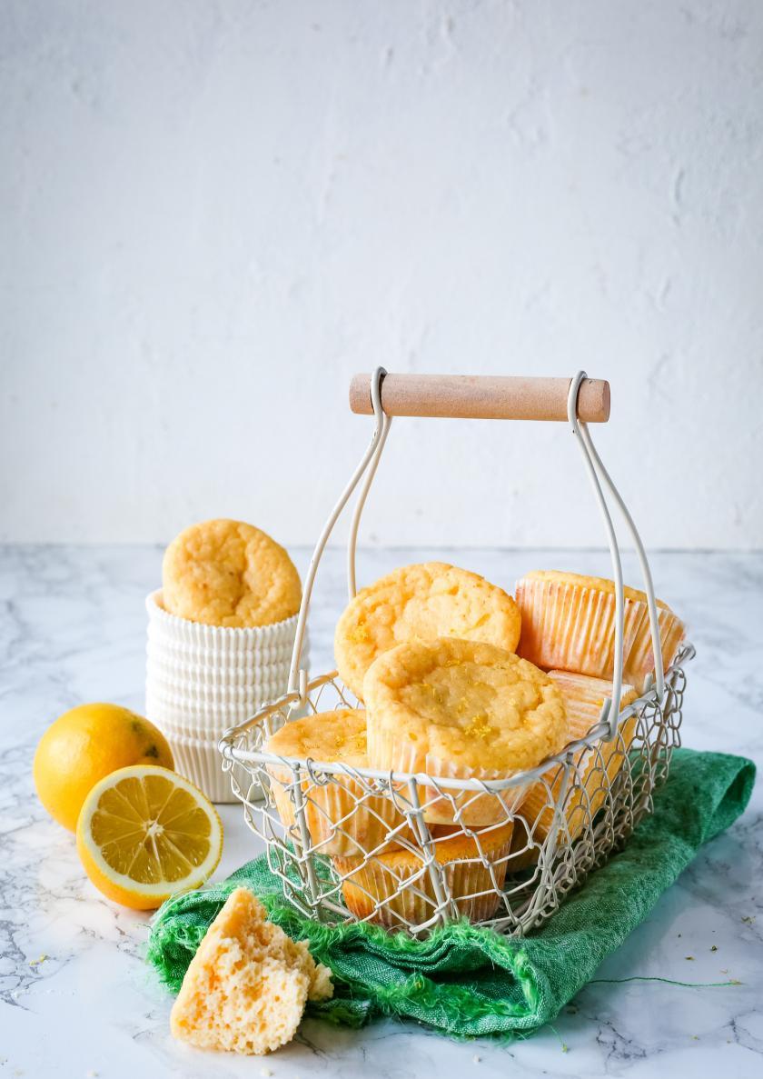 Low Carb Zitronen-Muffins liegen in einem Korb. Drumherum aufgeschnittene Zitronen als Dekoration.