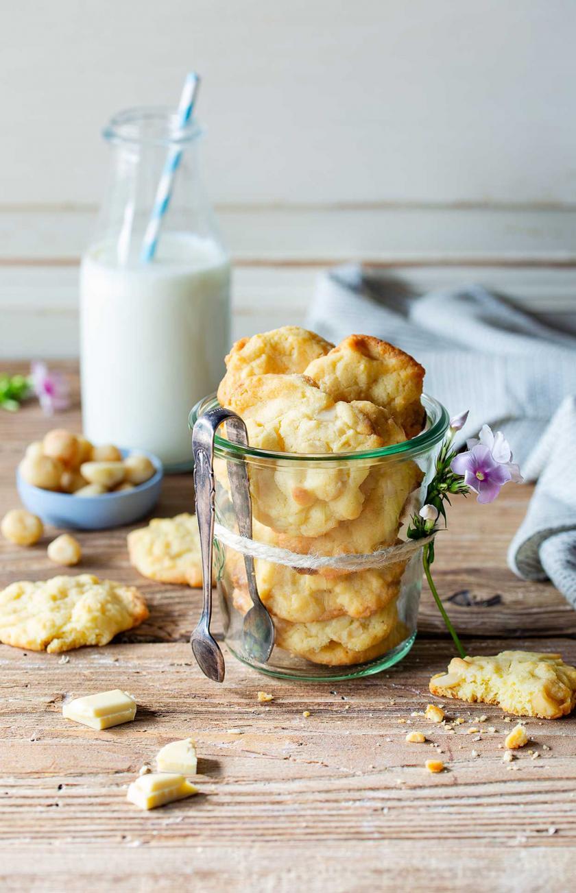 Macadamia Cookies in einem Glas geschichtet. Daneben Milch und Krümel.