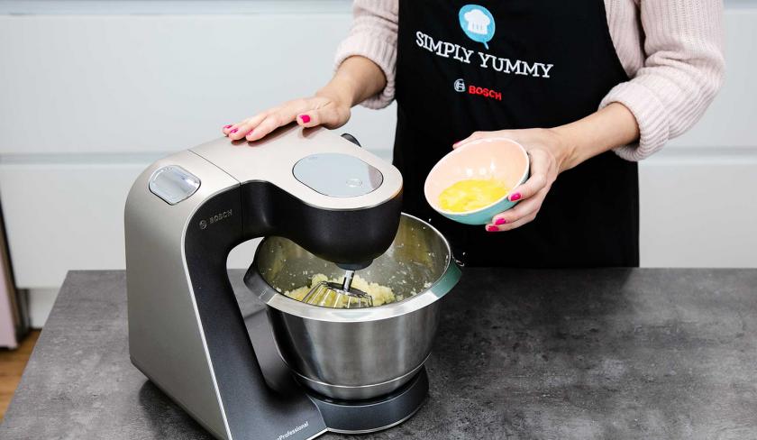 Für den Teig der Macadamia Cookies werden Eier in die Rührschüssel einer Küchenmaschine gegeben.