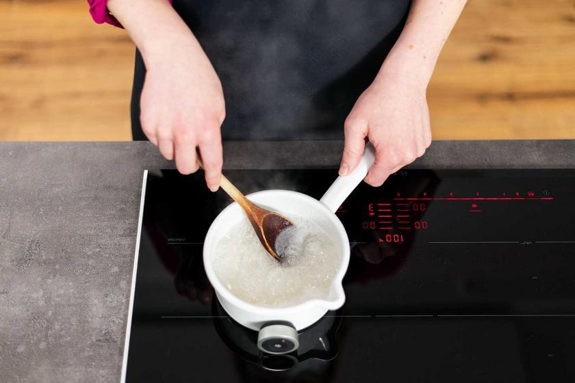 Zuckerguss für das Magenbrot wird in einem Topf gerührt.