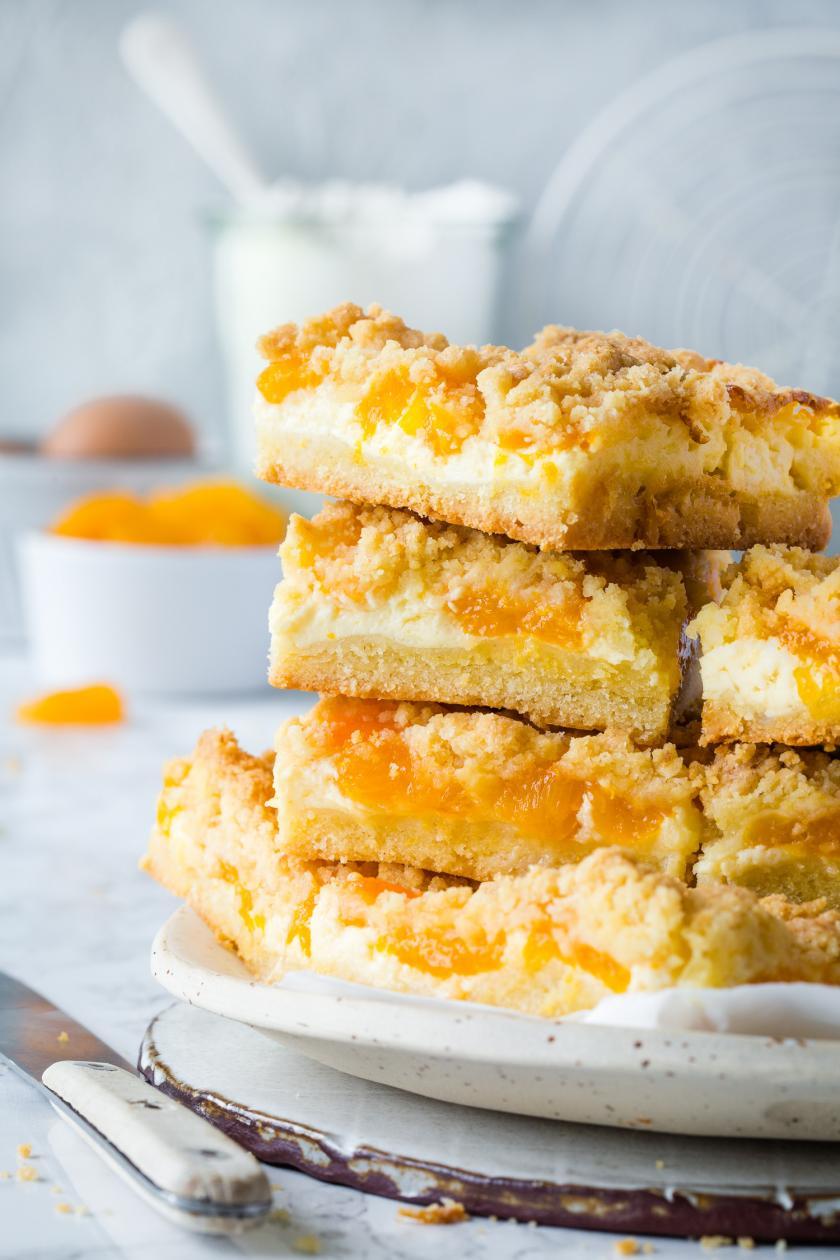 Mehrere Stücke Mandarinen-Streusel-Kuchen übereinandergestapelt.