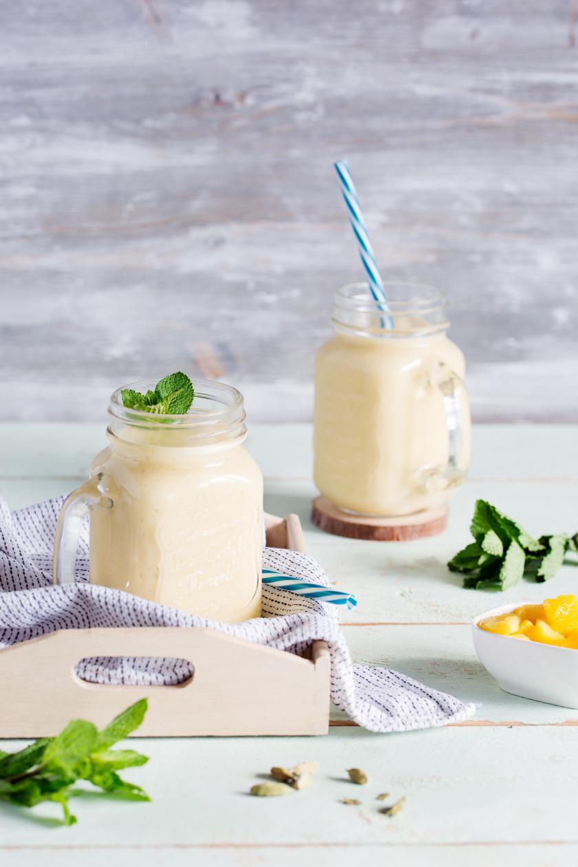 Gelber Mango-Lassi mit Kokosmilch in zwei Gläsern mit Strohhalm.