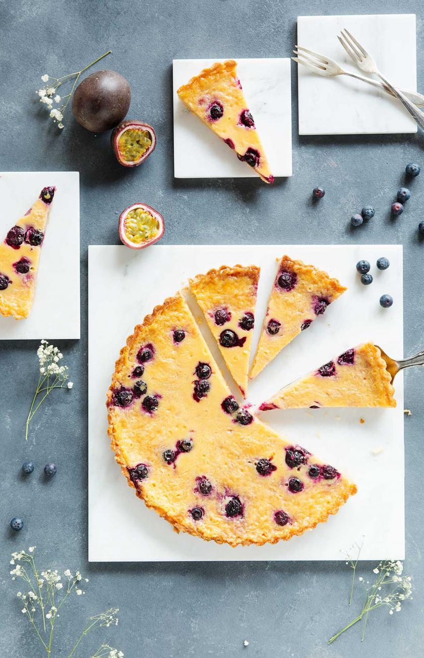 Maracuja-Tarte mit Blaubeeren angeschnitten auf einer Kuchenplatte.