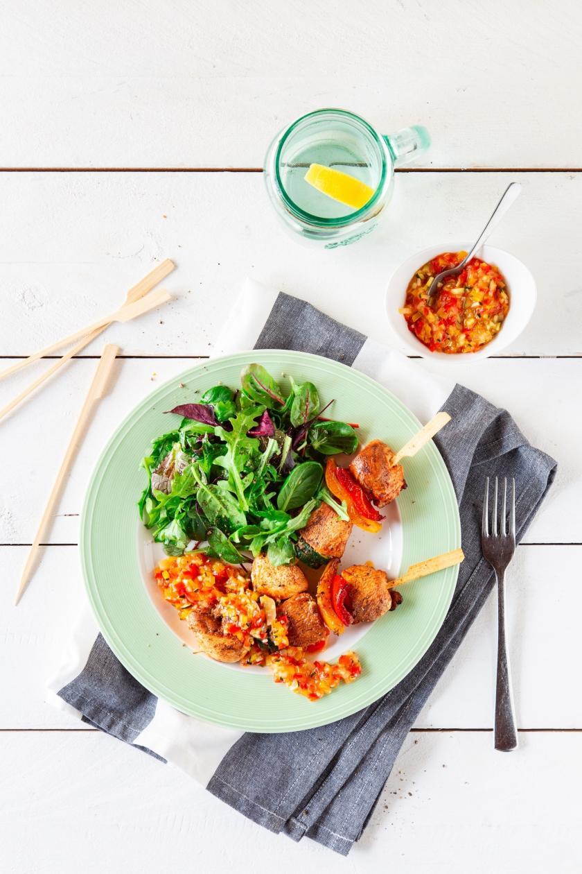 Hähnchenspieße mit Chutney und Salat auf Teller.