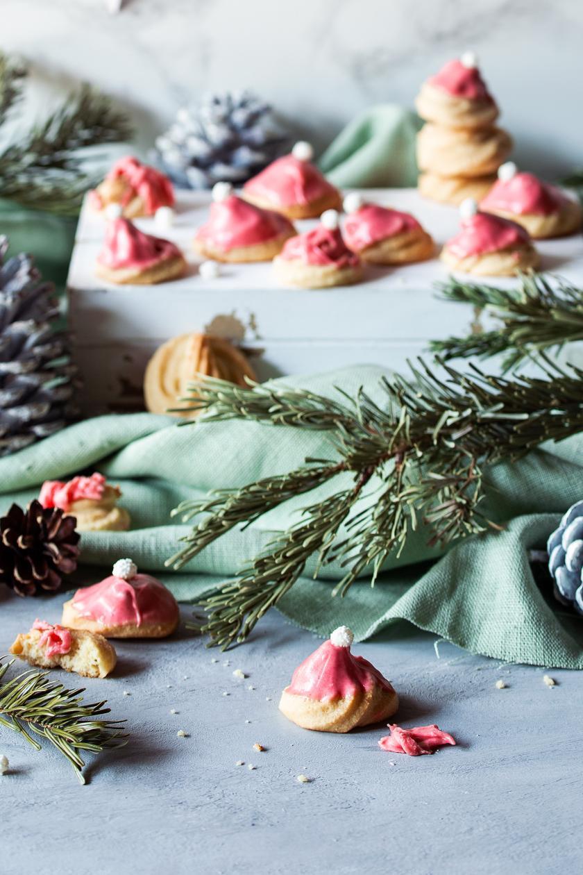 Viele Marzipan-Kekse auf einem Weihnachtstisch verteilt.