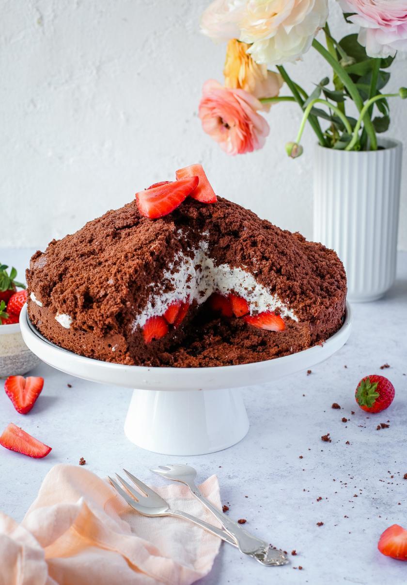 Maulwurfkuchen mit Erdbeeren auf einer Tortenplatte und angeschnitten