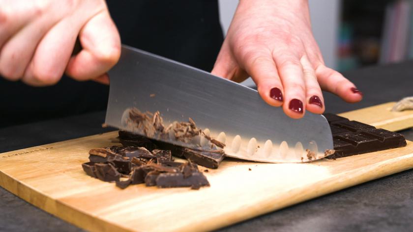 Für den Teig der Milchreis-Brownies wird Schokolade gehackt.