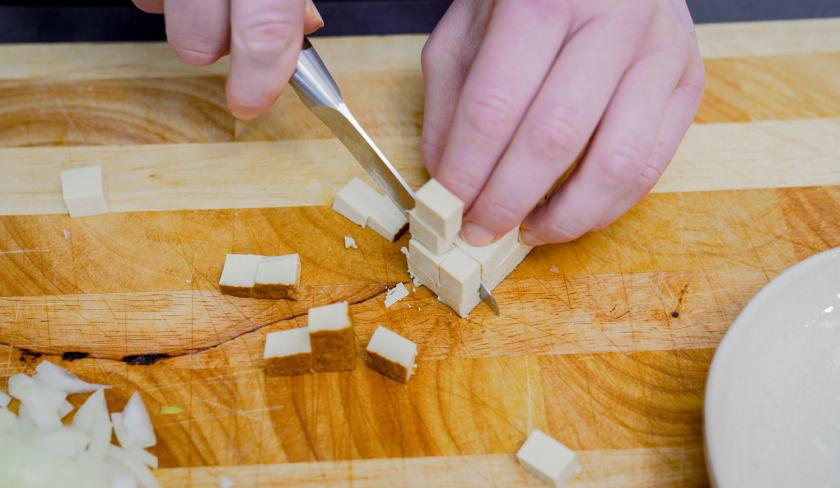 Für die Füllung der Mini-Quiche wird Räuchertofu geschnitten.