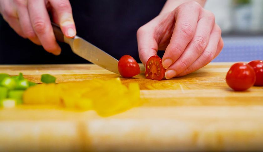 Für die Füllung der Mini-Quiche werden Tomaten auf einem Holzbrett halbiert.