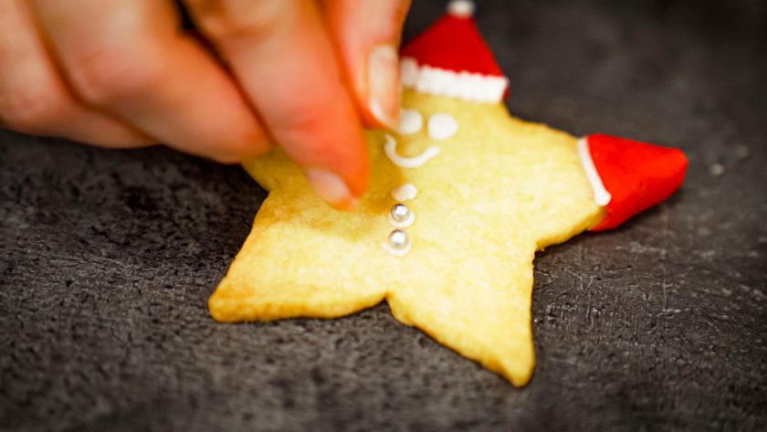 Die Nikolausplätzchen werden mit Zuckerperlen verziert.