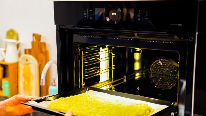 Das Blech mit den Nussecken mit Marzipan wird in den Ofen gegeben.