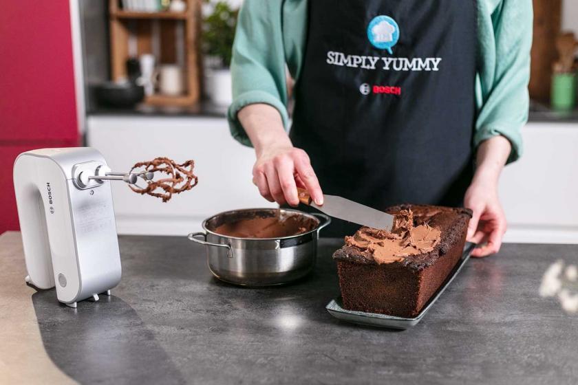 Der Nutella-Kuchen mit Schmand wird mit Ganache eingestrichen.
