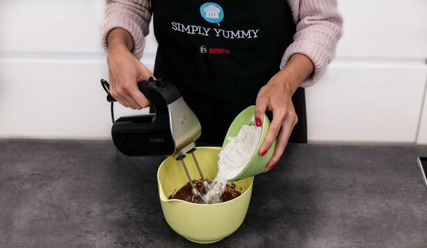 Für die Nutella-Plätzchen wird Mehl zur Masse in die Schüssel gegeben.