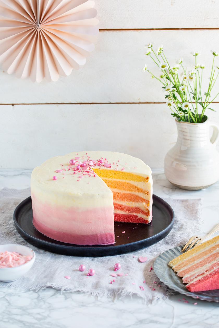Ombré Torte angeschnitten auf einer Kuchenplatte.