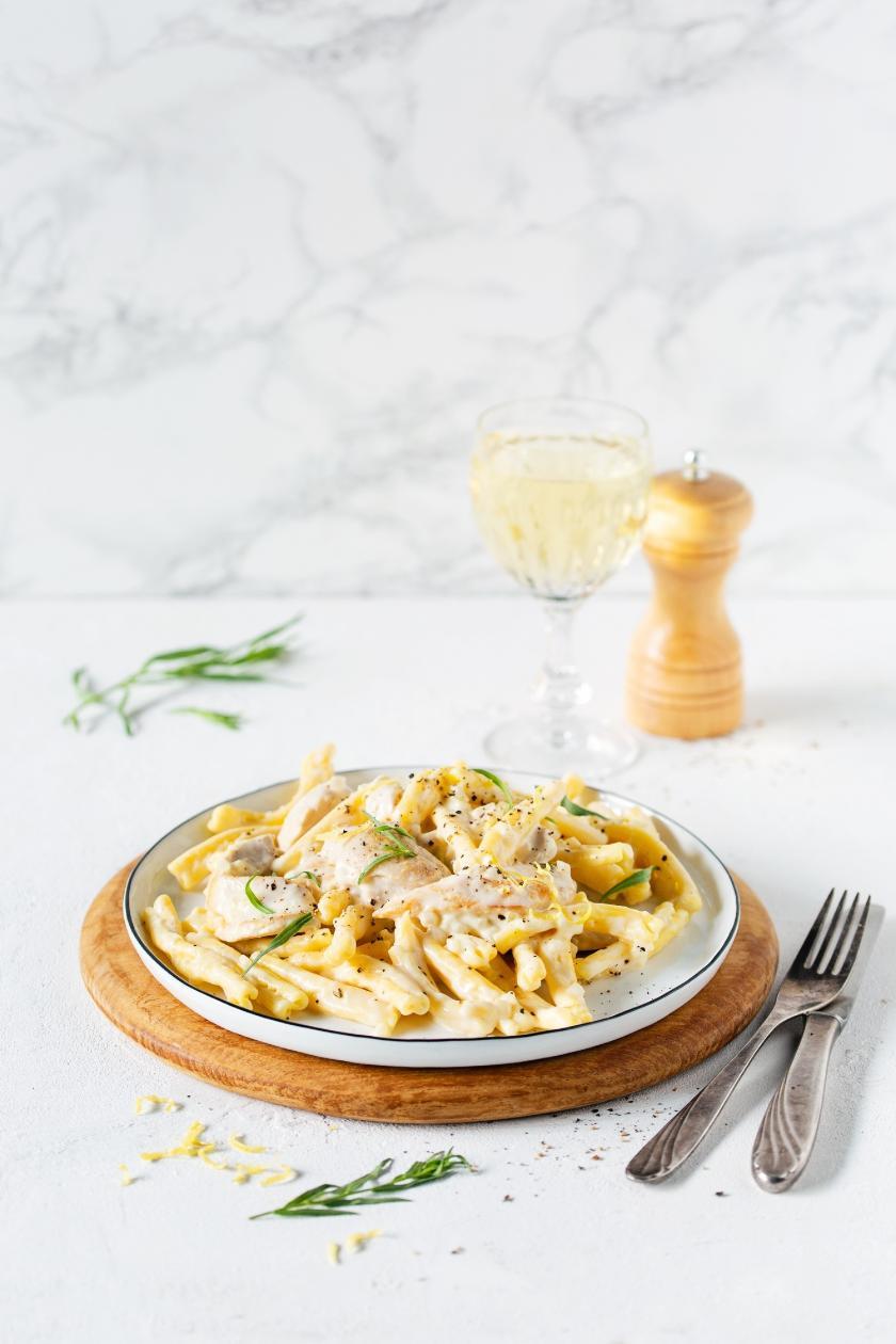 Pasta auf Teller mit Hähnchen in Sahne-Weißweinsauce