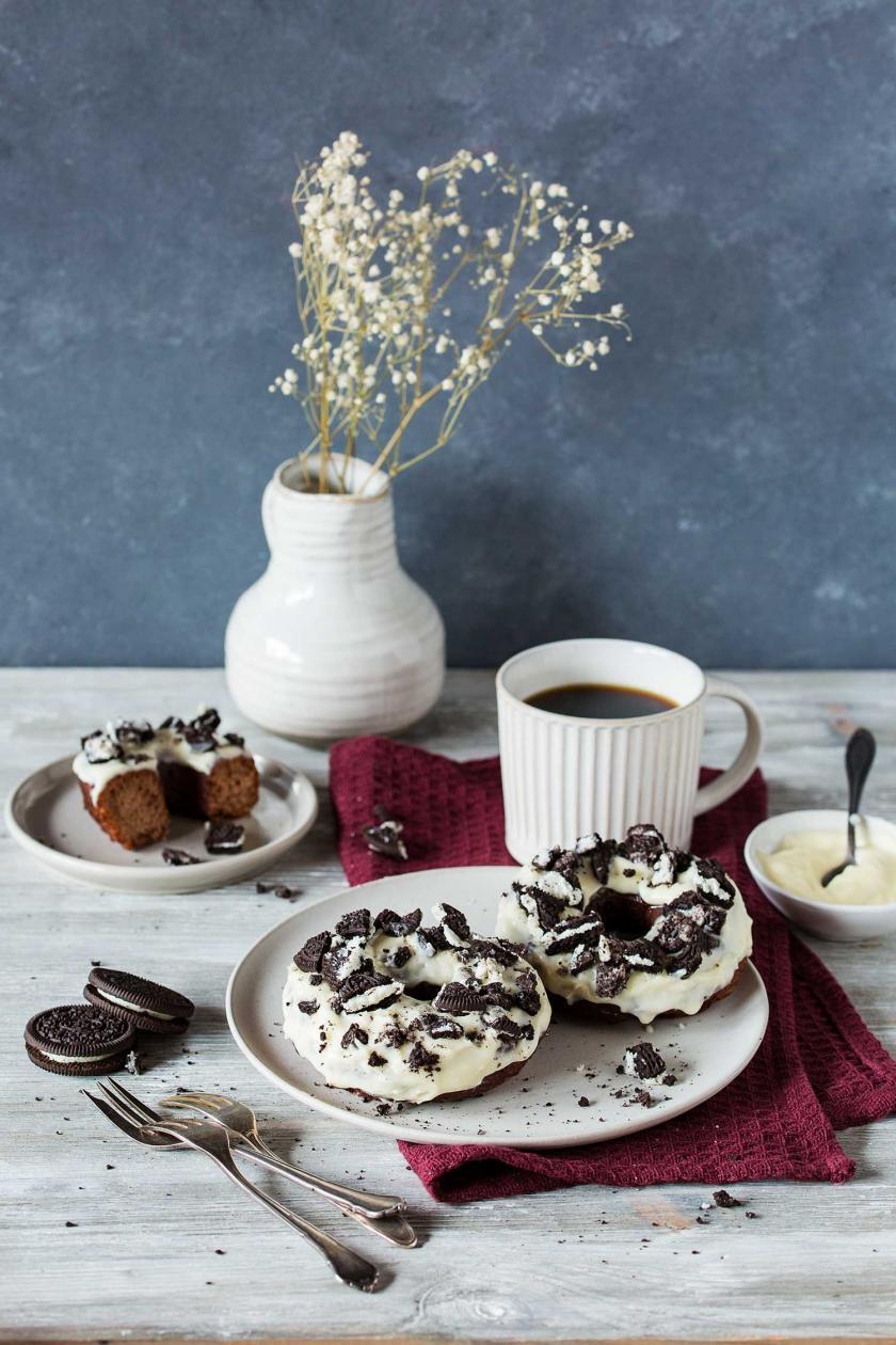 Zwei Oreo-Donuts auf einem Teller auf einem gedeckten Kaffeetisch.