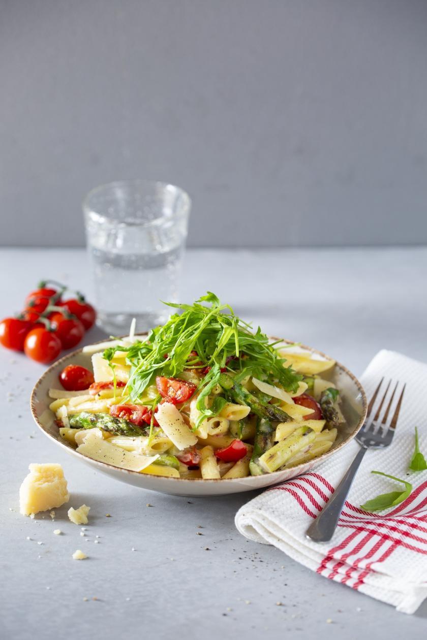 Pasta mit grünem Spargel und Rucola auf einem Teller angerichtet.