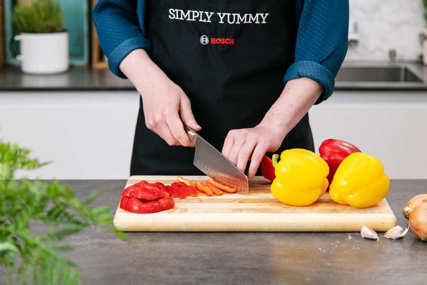 Paprika werden auf einem Brett geschnitten.
