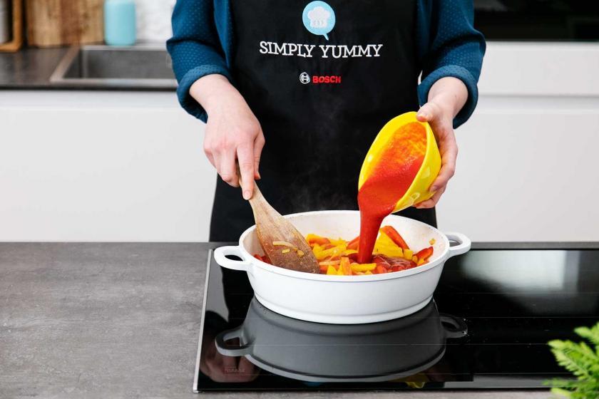 Passierte Tomaten werden zur Peperonata in die Pfanne gegeben.