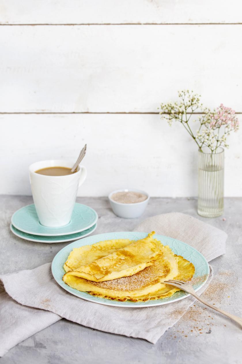Mehrere Pfannkuchen ohne Ei sind übereinander gestapelt auf einemTeller mit Gabel.