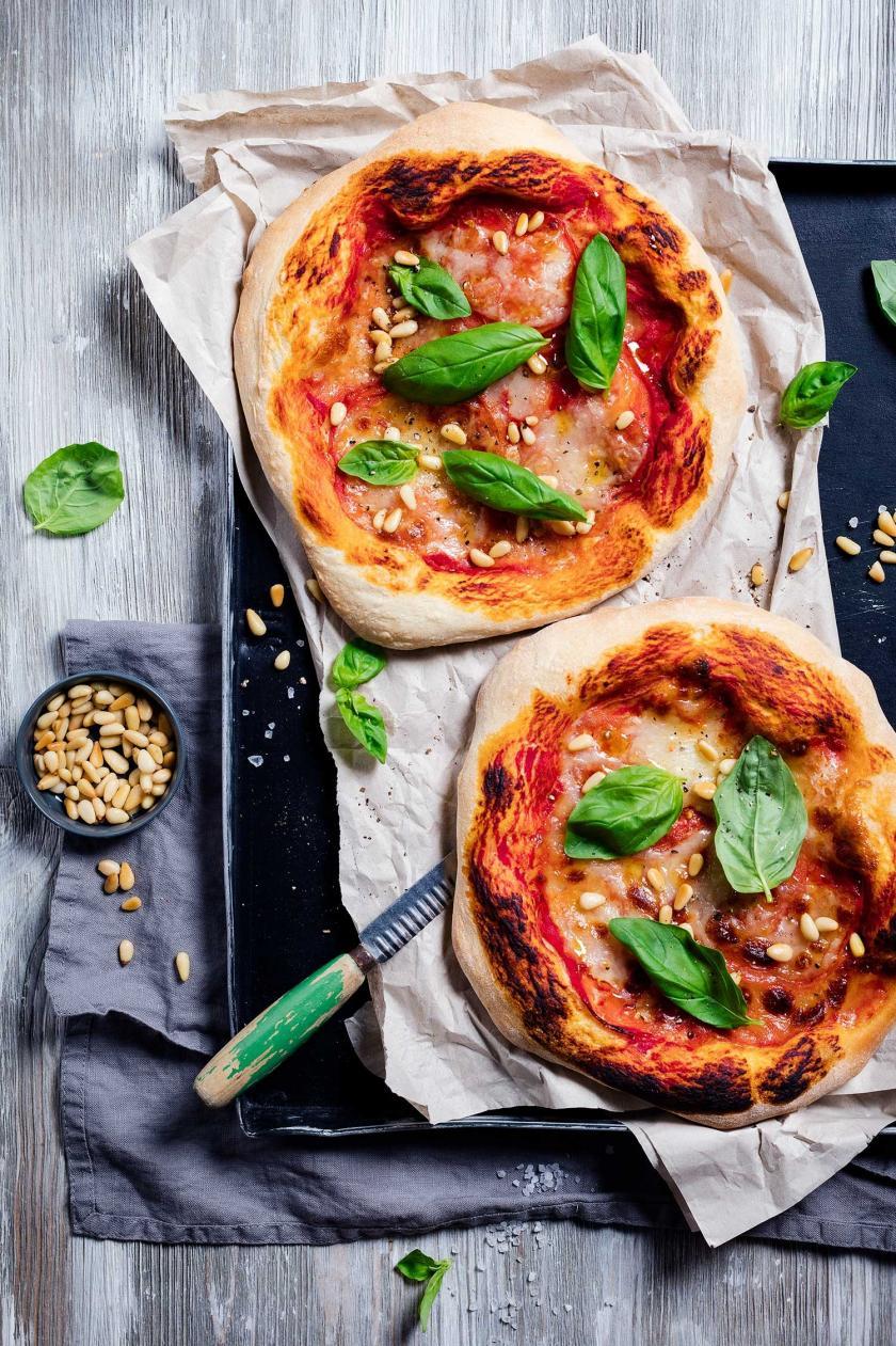 Zwei Pizzen Caprese im Ganzen auf Backblech mit Messer.