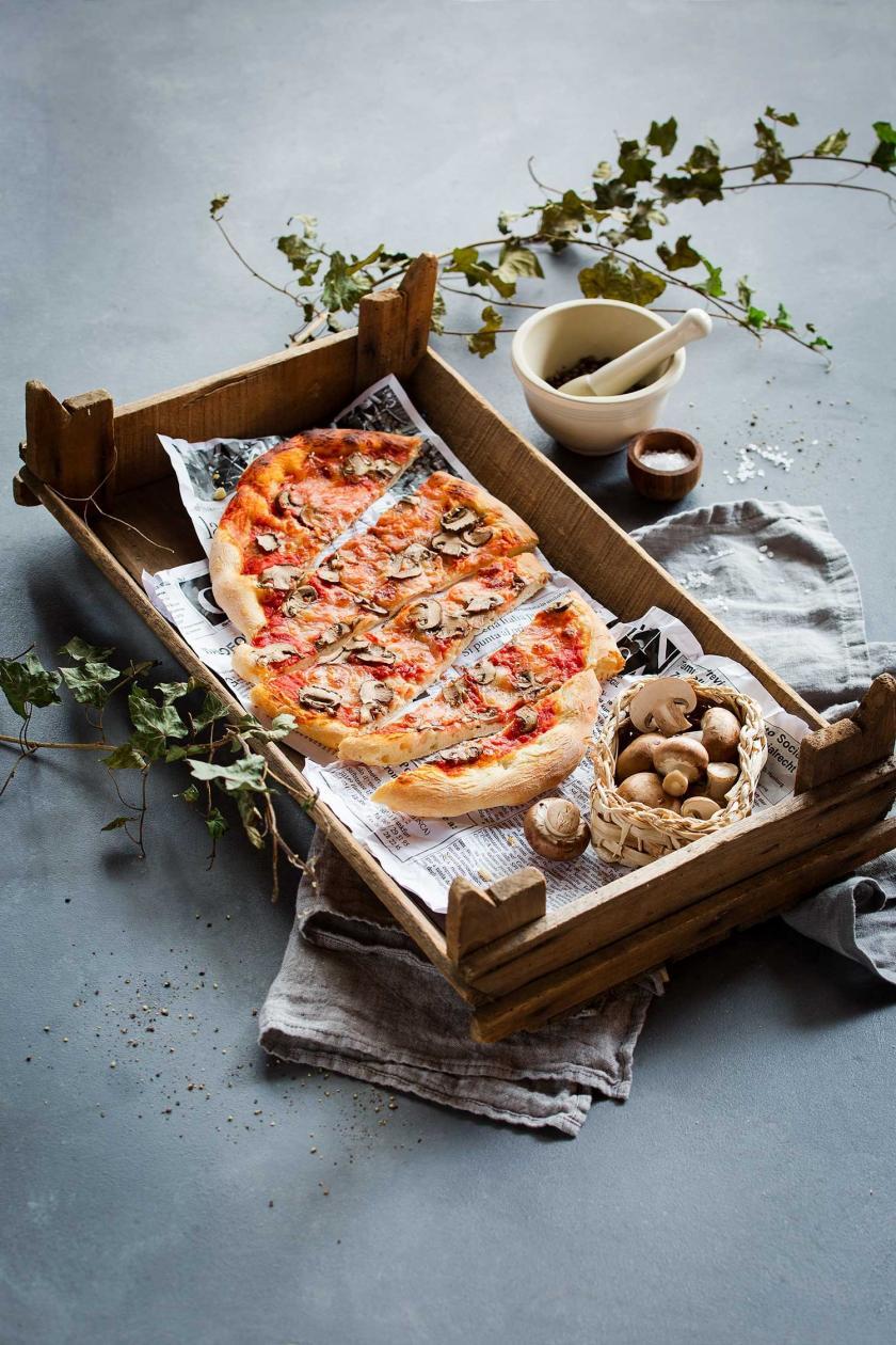 Pizza Funghi auf Zeitungspapier in einer Kiste. Daneben Pilze.