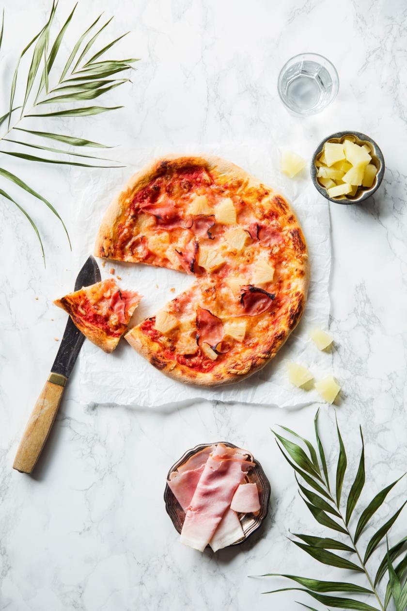 Pizza Hawaii angeschnitten mit Messer und Stück auf Holztisch.
