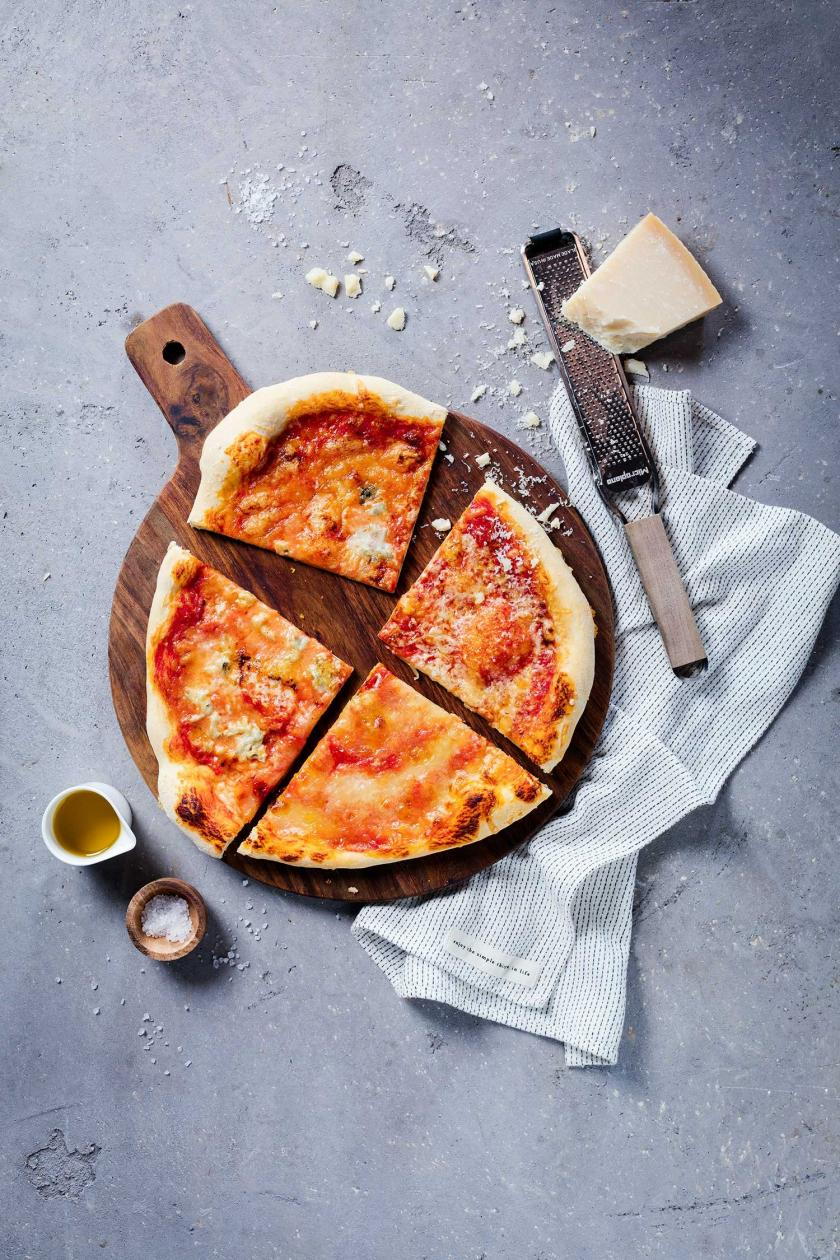 Pizza Quattro Formaggi geviertelt auf einem Holzbrett.