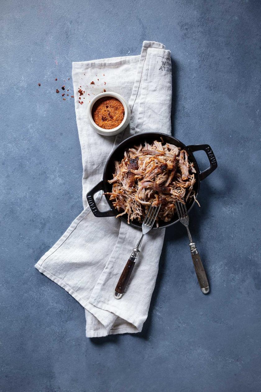 Pulled Pork in Pfanne auf weißem Küchentuch und Rub.