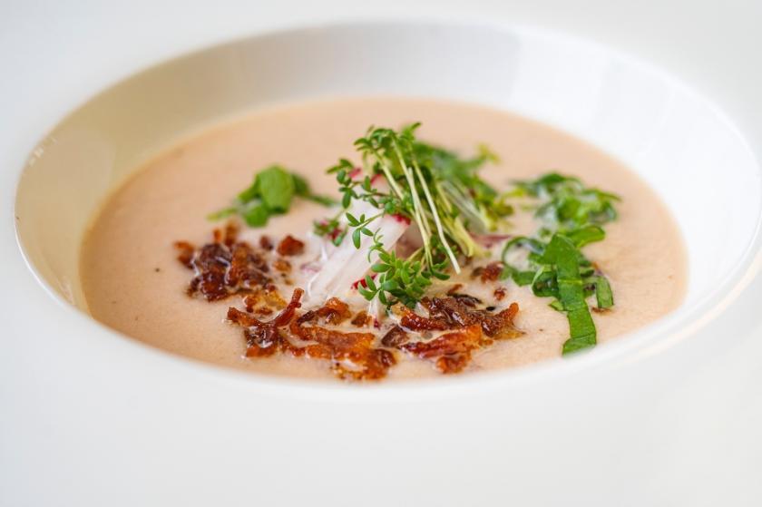 Radieschensuppe in weißem Suppenteller mit Bacon.