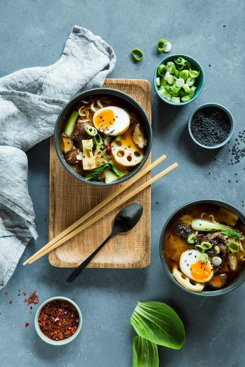 Ramen Suppe in einer Schüssel mit Stäbchen und Zutaten drum herum.
