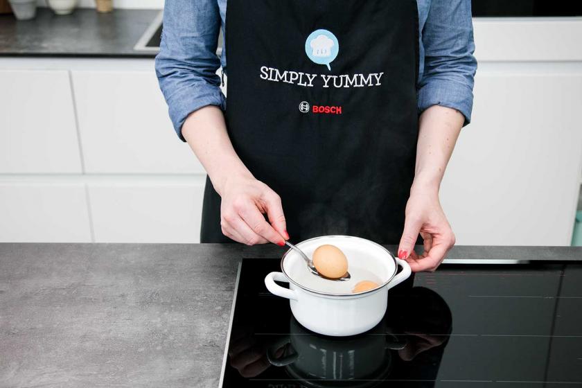 Für die Ramen Suppe wird ein Ei auf einem Löffel in einen Topf gegeben.
