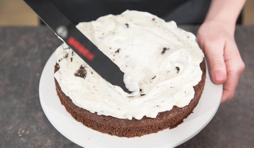 Die Füllung für die Oreo Torte wird auf einen Boden verstrichen.