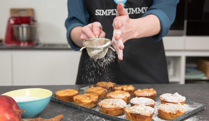 Puderzucker wird über die Apfel-Zimt-Muffins gestäubt.