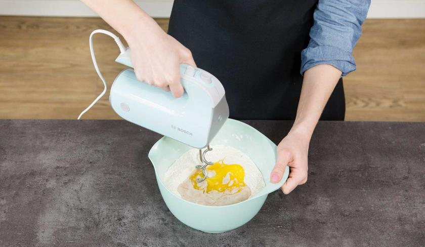 In einer Schüssel wird der Teig für den Kirsch-Streuselkuchen mit einem Mixer verrührt.