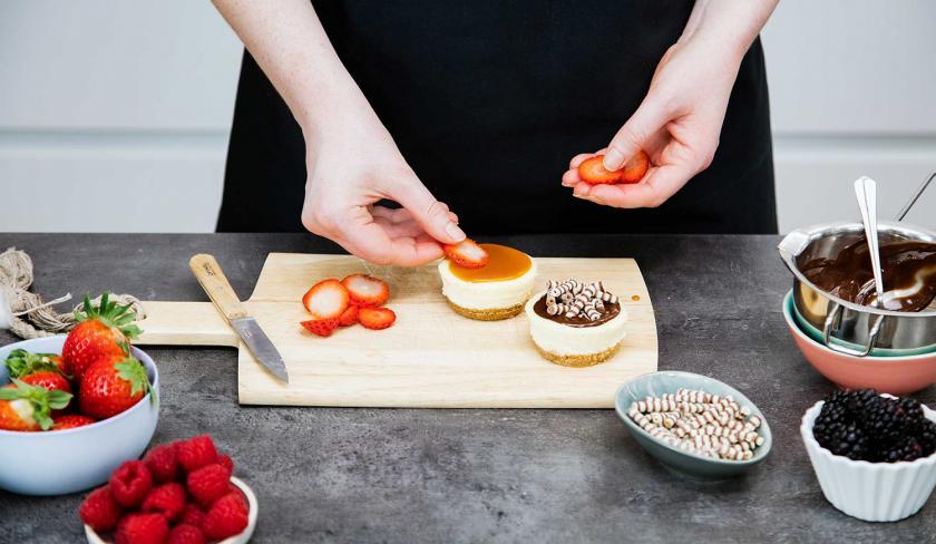 Cheesecake-Muffins werden mit Erdbeerscheiben belegt.
