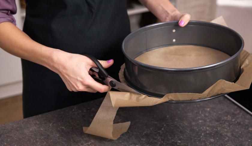 Eine Springform wird mit Backpapier ausgelegt zum Backen der Erdbeer-Joghurt-Torte.