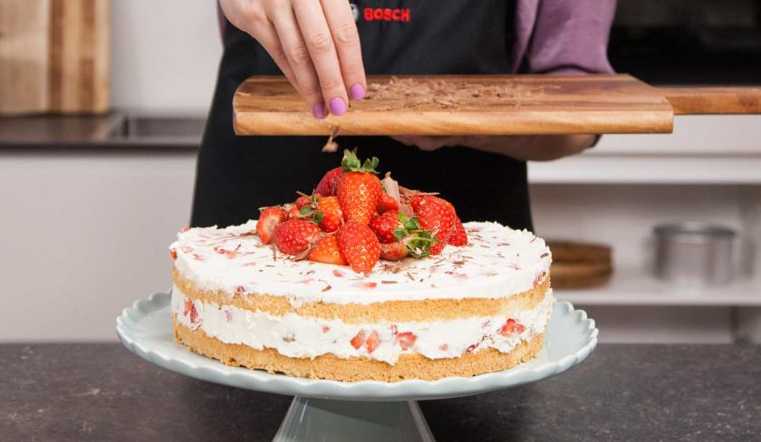Gehackte Schokolade wird auf die Erdbeer-Joghurt-Torte gestreut.