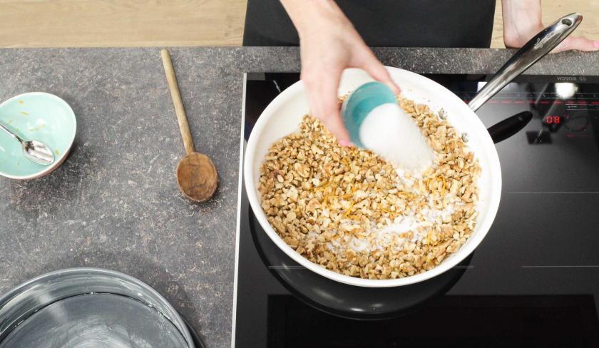 Für den Apfel-Walnuss-Kuchen werden Nüsse in einer Pfanne mit Zucker karamellisiert.
