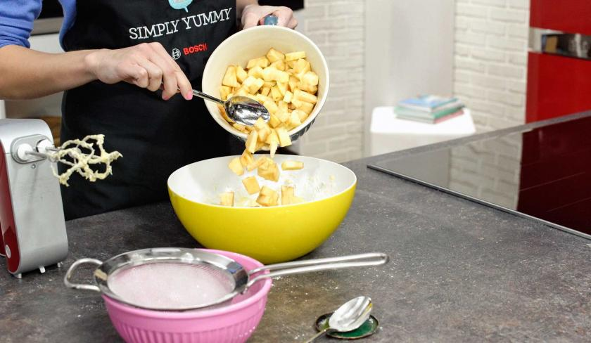 Für den Apfel-Walnuss-Kuchen werden geschnittene Äpfel in den Teig eingerührt.
