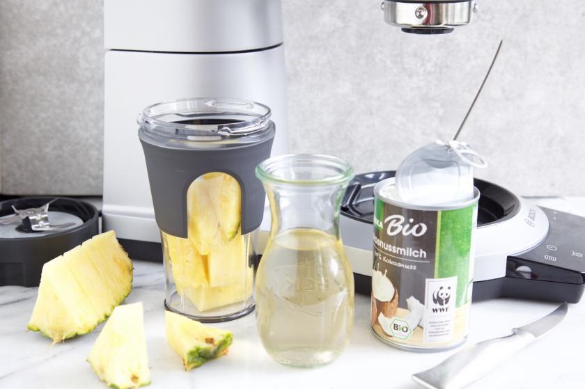 Ananas und Kokosmilch vor Hochleistungsmixer für Ananas-Smoothie