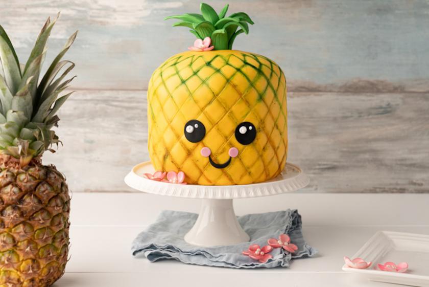 Ananas-Motivtorte mit Gesicht auf weißer Tortenplatte.