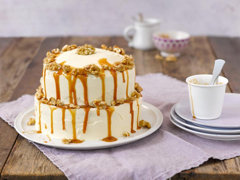Apfel-Walnuss-Torte mit Karamell auf einem Kuchenteller.