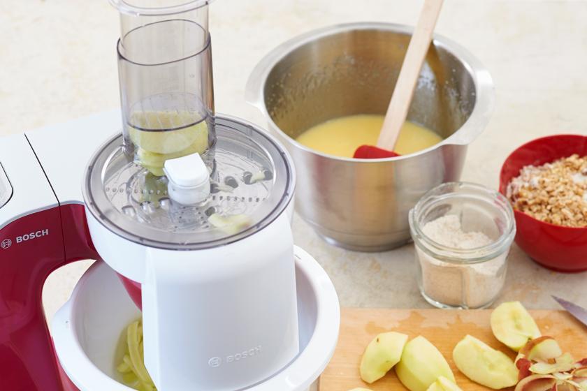 Für die Apfel-Walnuss-Torte werden Äpfel in einer Küchenmaschine gerieben.