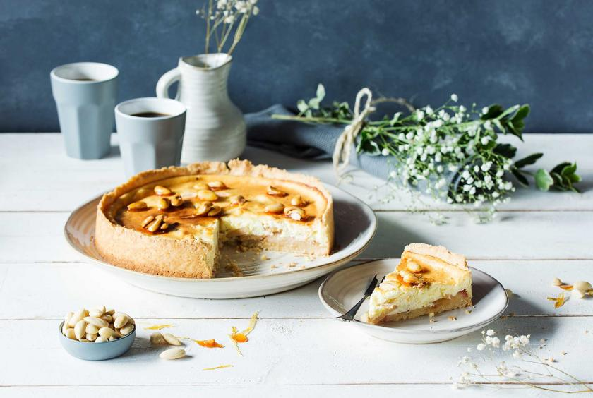 Apfelkuchen mit Quark angeschnitten auf einem Kuchenteller. Davor ein Teller mit einem Stück drauf.