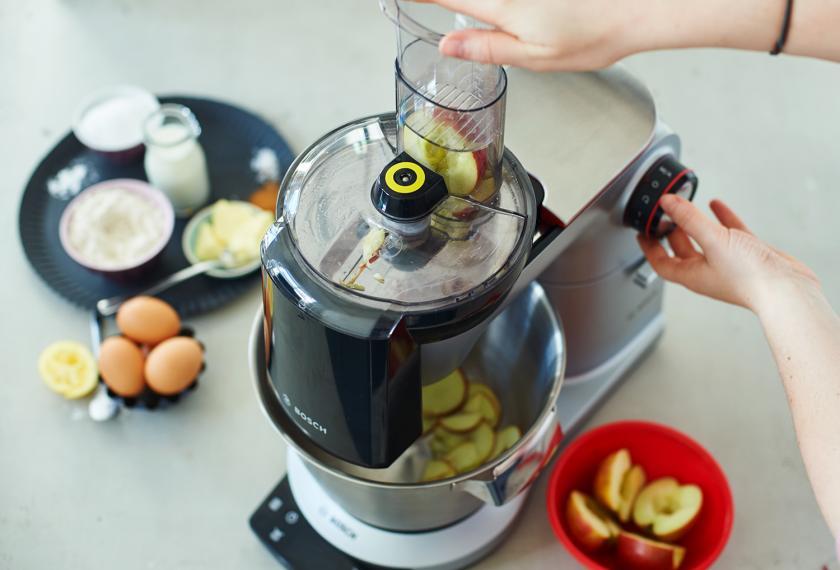 Für Apfelpfannkuchen werden Äpfel in einer Küchenmaschine gehobelt.