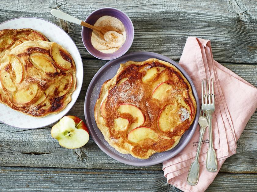 Zwei Apfelpfannkuchen auf Tellern angerichtet.