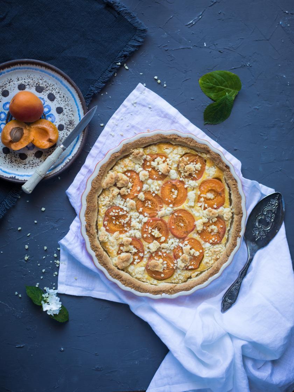 Die Aprikosentarte steht auf einem gedeckten Tisch. Im Hintergrund liegen aufgeschnittene Aprikosen auf einem Teller.