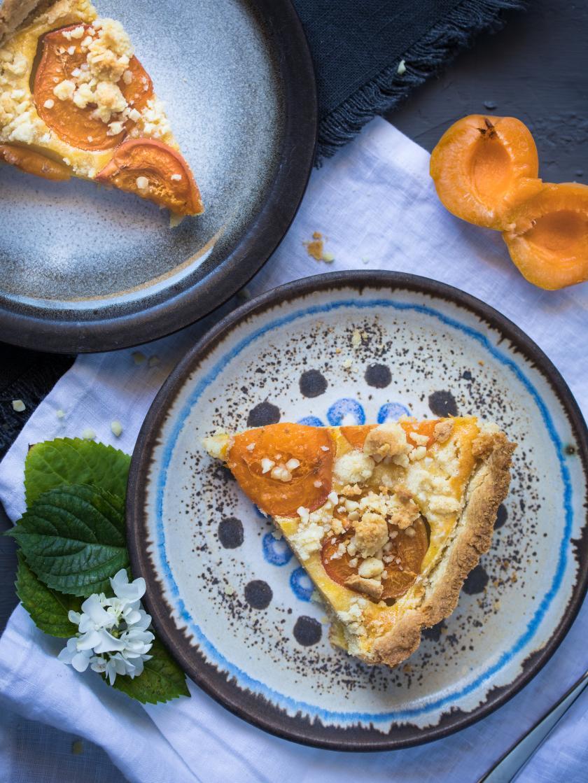 Ein Stück Aprikosentarte liegt auf einem gemusterten Teller.